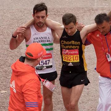 Image: London Marathon runner Matt Rees helps fellow participant David Wyeth to cross the finish line, April 23, 2017.