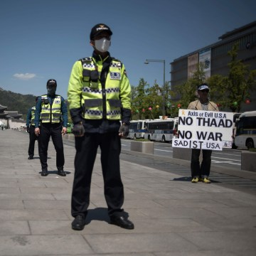 Image: A protester holds a placard denouncing the THAAD anti-missile system