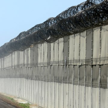 Image: A U.S. Customs and Border Patrol officer patrols along the border