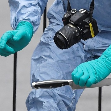 Image: A forensic investigator recovers a knife after man was arrested in Westminster