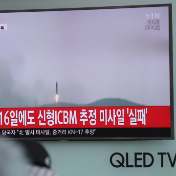 Image: A man watches a TV news program reporting about North Korea's missile firing with a file footage in Seoul.