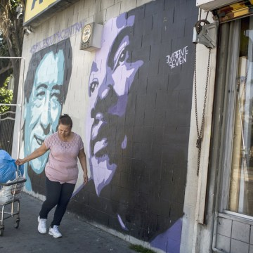 Image: A woman walks past a mural of Cesar Chavez, left, and Martin Luther King Jr., right, in South Central Los Angeles on April 28, 2017, in California.