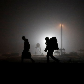 Image: Migrants walk along railway tracks after crossing the Canada-U.S. border in Emerson