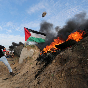 Image: Palestinian protester uses a sling to hurl stones towards Israeli troops during clashes near the border between Israel and Central Gaza Strip
