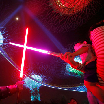 "Image: A fan dressed in a costume ""duels"" with a fan during activities to mark ""May the 4th"" Star Wars Day at Gardens by the Bay in Singapore"