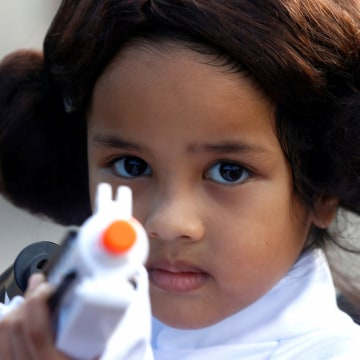 """Image: Leia Farid, 4, poses for photos during activities to mark """"May the 4th"""" Star Wars Day at Gardens by the Bay in Singapore"""