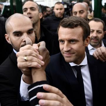 Image: Emmanuel Macron shakes hands in Sarcelles, near Paris