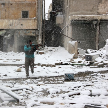 Image: A rebel fighter aims his weapon as he stands amidst snow during clashes with Syrian pro-government forces