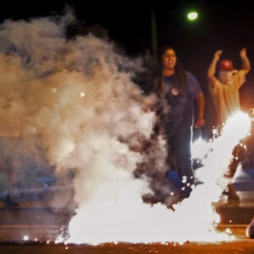 Image: Edward Crawford returns a tear gas canister fired by police