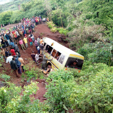 Image: Residents gather at the scene of an accident that killed schoolchildren, teachers and a minibus driver along the Arusha-Karatu highway in Tanzania's northern tourist region of Arusha