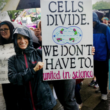 """Image: Alison Wolf of Richmond, Virginia studies tobacco and nicotine at Virginia Commonwealth University. She said she wanted to stress that science is part of society's mainstream. She carried a sign saying, """"Cells divide. Do we have to?"""""""