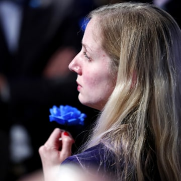 Image: A supporter of Marine Le Pen holds a blue flower