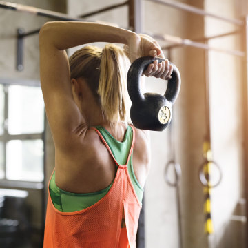 Image: Woman in gym working her arms with kettle bell
