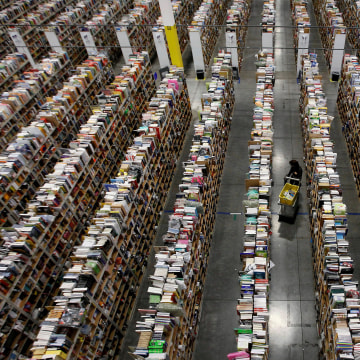 Image: A worker gathers items for delivery at Amazon's distribution center in Phoenix