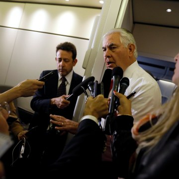 Image: Rex Tillerson speaks with reporters aboard Air Force One