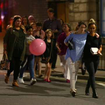 Image: Police escort members of the public from the Manchester Arena