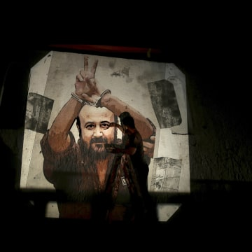 Image: A Palestinian paints an image of Marwan Barghouti on a wall on the streets of Gaza City.