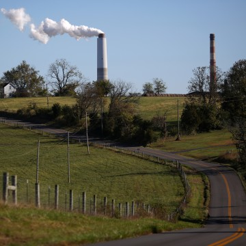 Image: A county road winds through farmland as emissions rise from a generating station