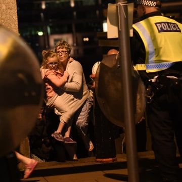 Image: People are lead to safety on Southwark Bridge in London
