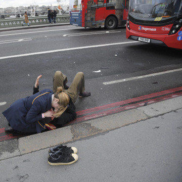 Image: A woman assists an injured person on Westminster Bridge in London