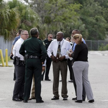 "Image: Authorities confer, June 5, 2017, near Orlando, Florida. Law enforcement authorities said there were ""multiple fatalities"" following a Monday morning shooting in an industrial area near Orlando."