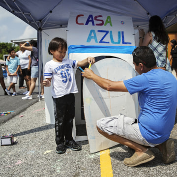 Image: Miguel helps out a boy as he participates in a public art project at a booth