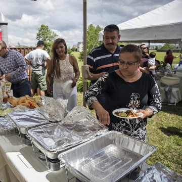 Image: Raul Garcia helps serve his home cooked barbecue