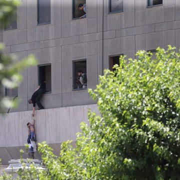 Image: Iranian policemen try to help some civilians fleeing from the parliament building during an attack in Tehran
