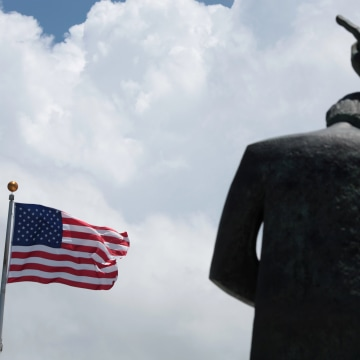 Image: The statue of St. John and the U.S. flag are seen outside the Capitol building in San Juan