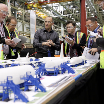 Image: Jason Clark (4th L), Vice President of Boeing 777 and 777X Operations, points to a model during a media tour of the 777 Wing Horizontal Build Line at Boeing's production facility in Everett, Washington