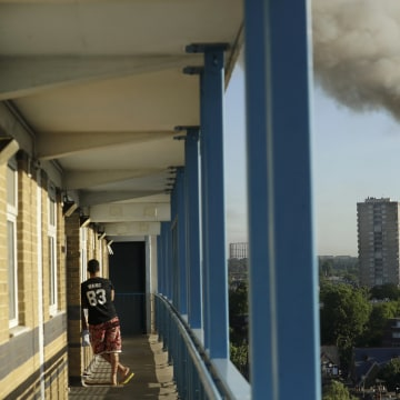 Image: A resident in a nearby building watches smoke rise from a building on fire in London