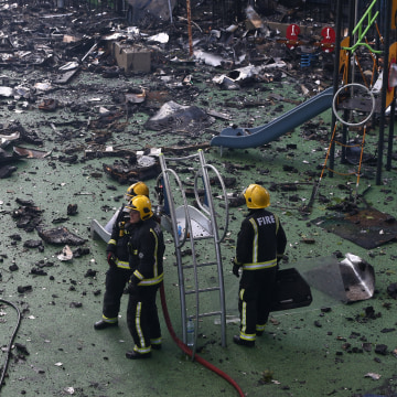 Image: Firefighters stand amid debris in a childrens playground near a tower block severly damaged by a serious fire, in north Kensington, West London
