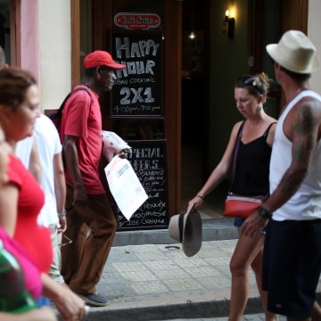 "Image: People walk past a bar and a sign advertising ""Happy hour"" in Havana"