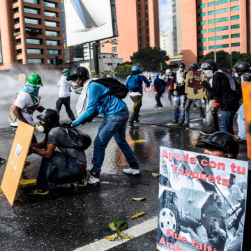 "Image: Opposition activists use makeshift shields as they clash with the police during the ""Towards Victory"" protest against the government of President Nicolas Maduro in Caracas on June 10, 2017."
