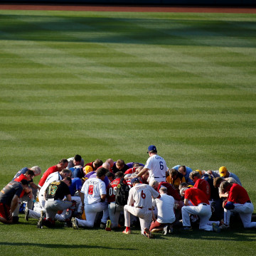 Image: Members of the Republican team pray before the Democrats and Republicans face off in the annual Congressional Baseball Game at Nationals Park in Washington