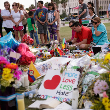 ORLANDO, FL - JUNE 14:  People visit the makeshift memorial for the victims of the Pulse Nightclub shooting lay at a makeshift memorial, June 14, 2016 in Orlando, Florida. The shooting at Pulse Nightclub, which killed 49 people and injured 53, is the wors