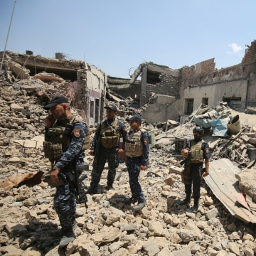 Image: Iraqi forces stand in the rubble of a building as they advance towards Mosul's Old City