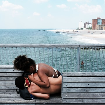 Image: Teenagers relax along the boardwalk on a hot day at Coney Island as sweltering summer temperatures grip New York City