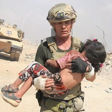 Image: Dave Eubank carries a young girl to safety in Mosul