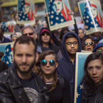 Image: People carry posters during a rally in support of Muslim Americans