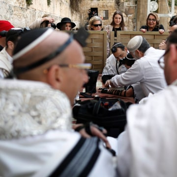 Image: Jewish women watch a religious ceremony on the men's side over a separation barrier at the Western Wall.