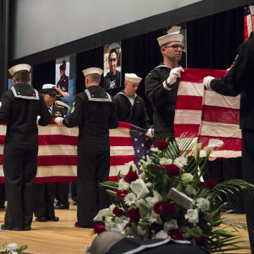 Image: Sailors fold seven U.S. flags during a memorial ceremony