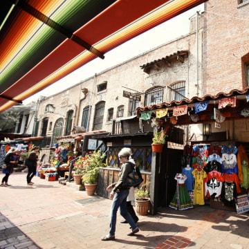 Image: Tourists shop at Olvera Street stores at El Pueblo de Los Angeles Historic  District in Los Angeles.