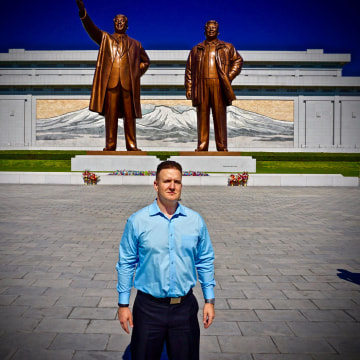 Image: Randy Williams poses in front of the Korean Revolution Museum building in Pyongyang