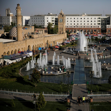 Image: People make their way on Shar Garden square in Erbil