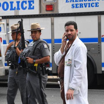 Image: A hospital staff member talks on his phone as he walks past police outside the Bronx-Lebanon Hospital