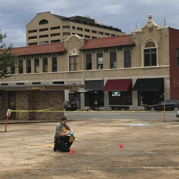 Image: An investigator collects evidence near an Arkansas nightclub