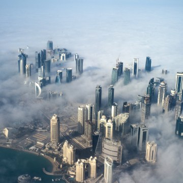 Image: An aerial view of high-rise buildings emerging through fog covering the skyline of Doha.