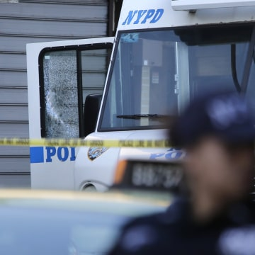 Image: An NYPD vehicle with a cracked window sits on the scene where a police officer was fatally shot