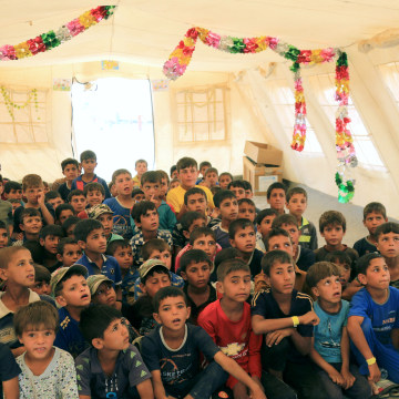 Image: Zaid Adil Sultan teaches a class for displaced Iraqi children in a tent school at tje Hammam al-Alil camp